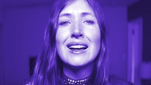 Kate Lyn Sheil faces the camera, tinged in blue light in the film She Dies Tomorrow