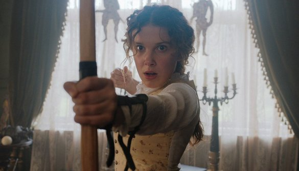 Millie Bobby Brown looks shocked after releasing an arrow from her bow in the movie Enola Holmes