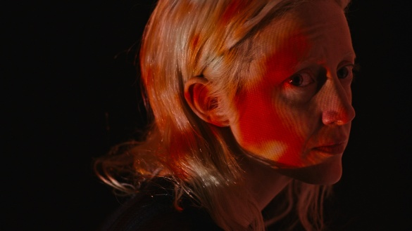 Andrea Riseborough looking worried and cast in an orange glow in the movie Possessor.