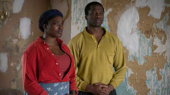 Wunmi Mosaku and Sope Dirisu stand next to walls with peeled-off wallpaper in film His House