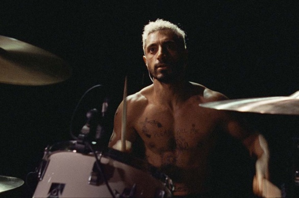 Riz Ahmed shirtless playing drums in the movie Sound of Metal