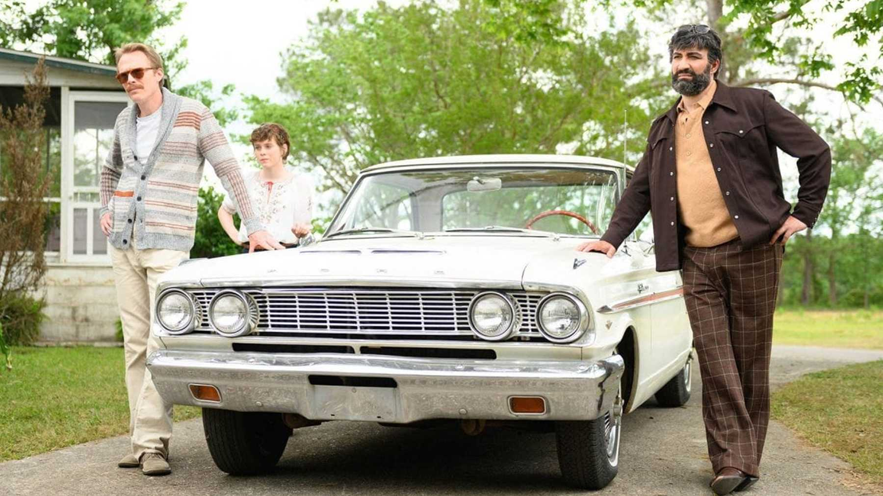 Paul Bettany, Sophia Lillis, and Peter Macdissi stand with their hands on a car in the movie Uncle Frank