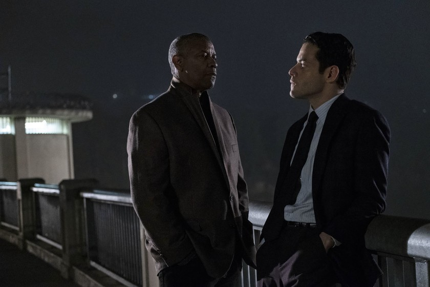 Denzel Washington and Rami Malek stand on a bridge at night talking closely in the movie The Little Things