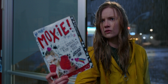 Hadley Robinson stands in the rain angrily holding her zine Moxie in the movie Moxie