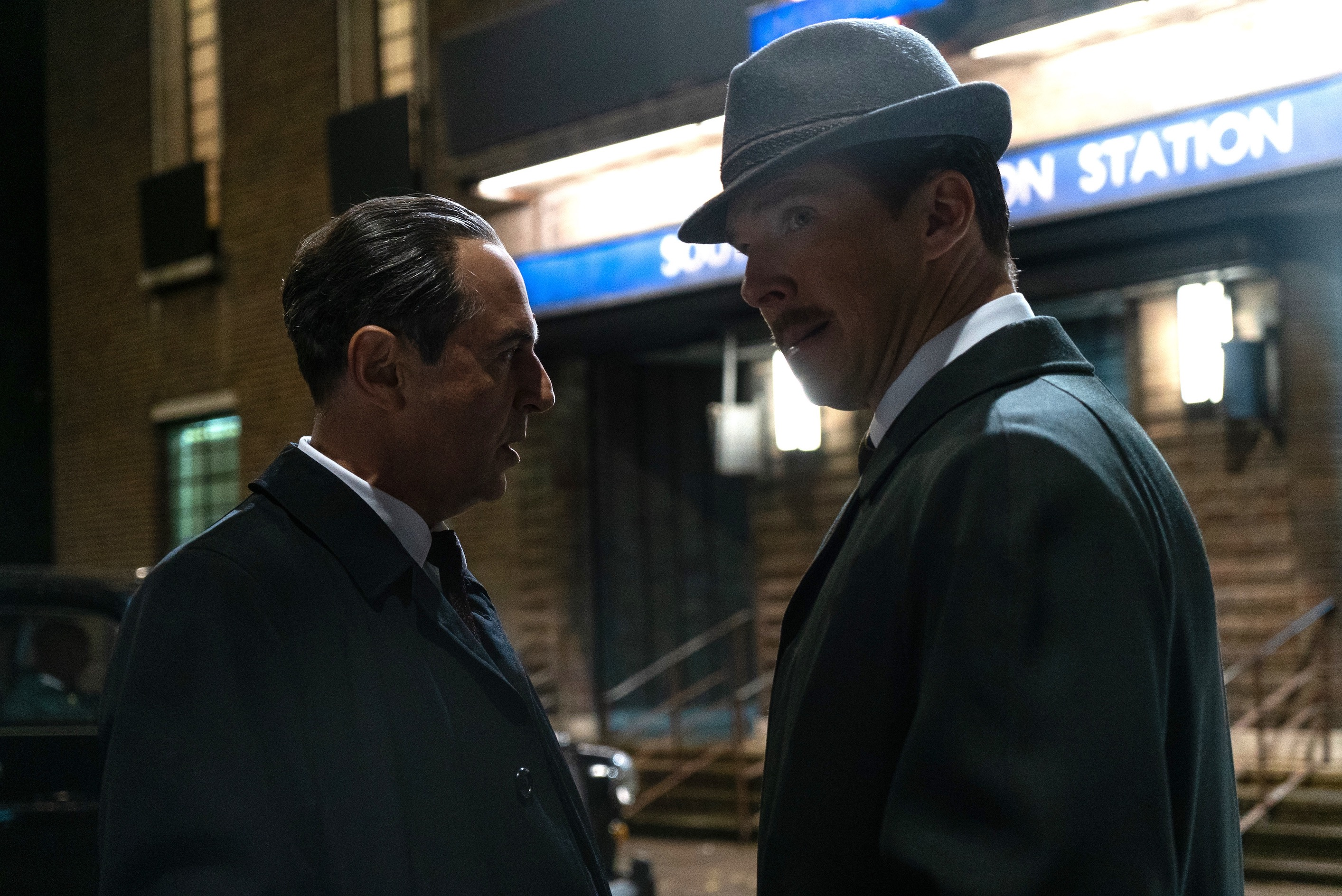 Merab Ninidze and Benedict Cumberbatch glance furtively as they talk quietly at night on a city street in the movie The Courier