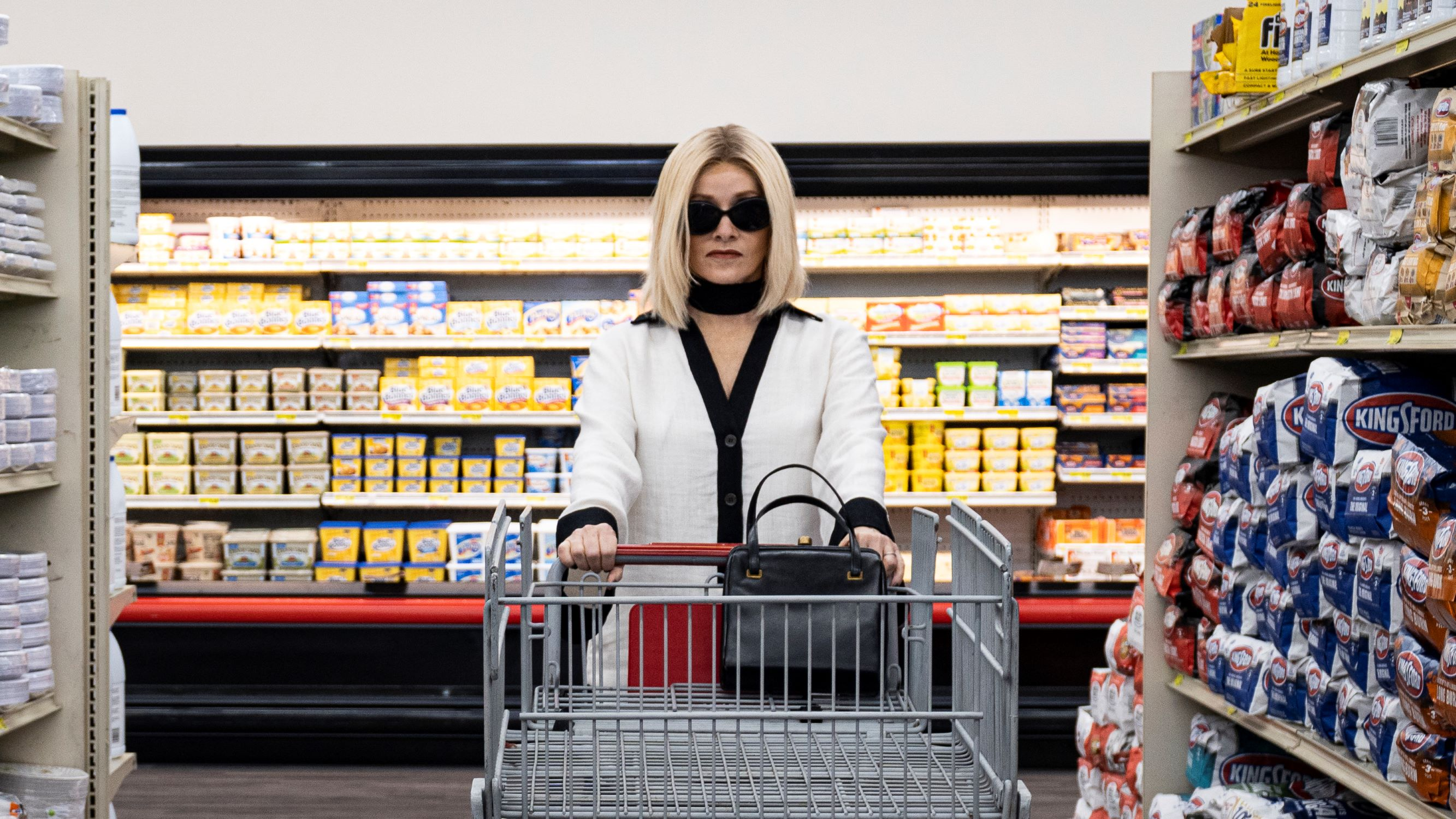 Barbara Crampton wearing sunglasses inside pushing a shopping cart at a grocery store in the horror movie Jakob's Wife