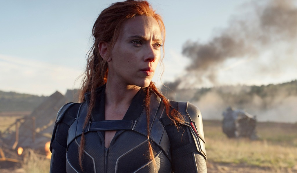 Scarlett Johansson squints into the distance as wreckage smolders around her in the movie Black Widow
