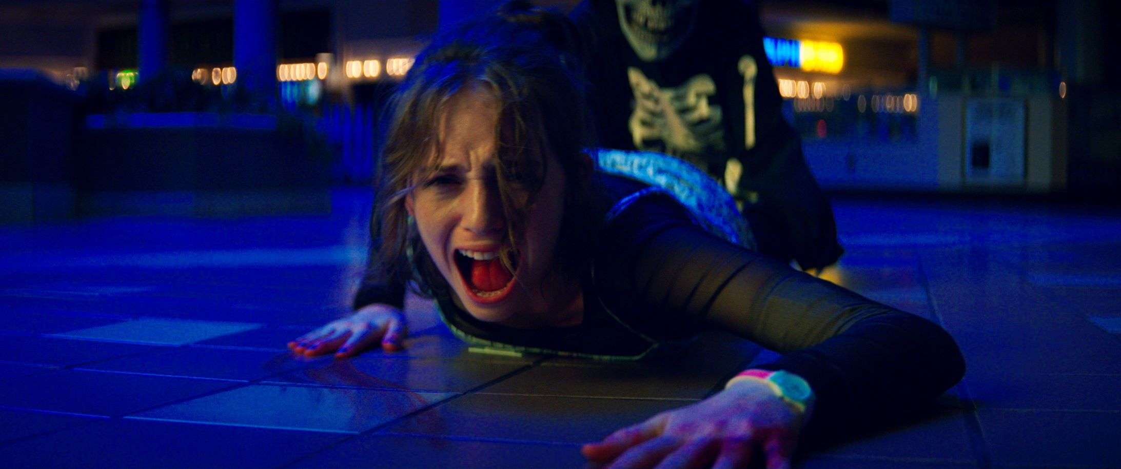 Maya Hawke crawls away screaming while a killer wearing a skull mask grabs onto her in Leigh Janiak's FEAR STREET: PART ONE - 1994.
