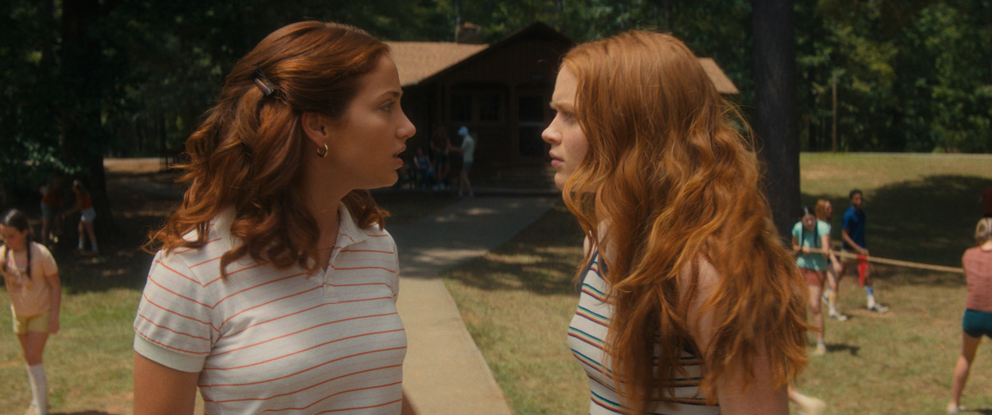 Emily Rudd and Sadie Sink stand facing each other mid-argument in the movie in FEAR STREET: PART TWO - 1978