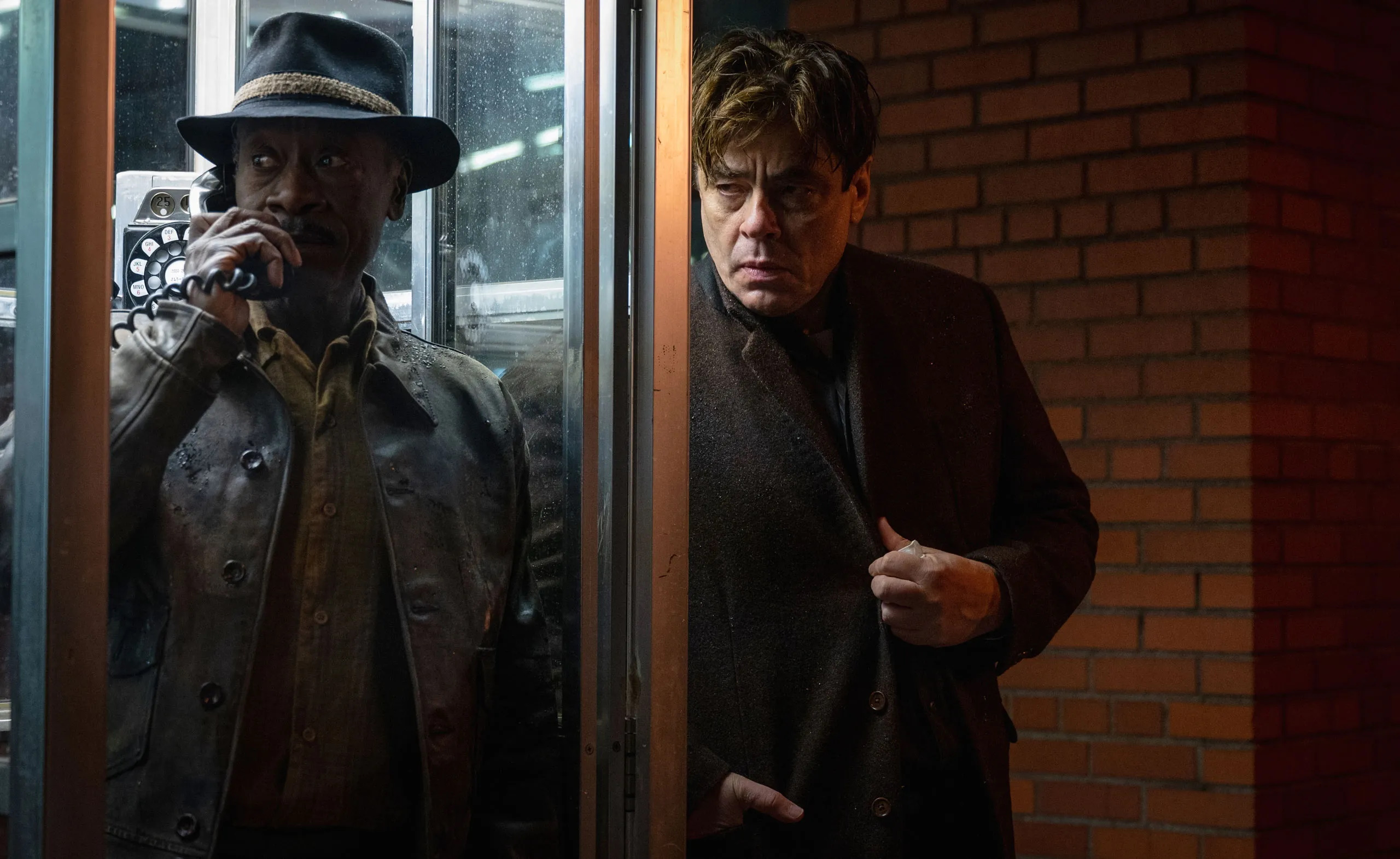 Don Cheadle talks on the phone from a phone book while Benicio del Toro waits anxiously outside it in the movie No Sudden Move