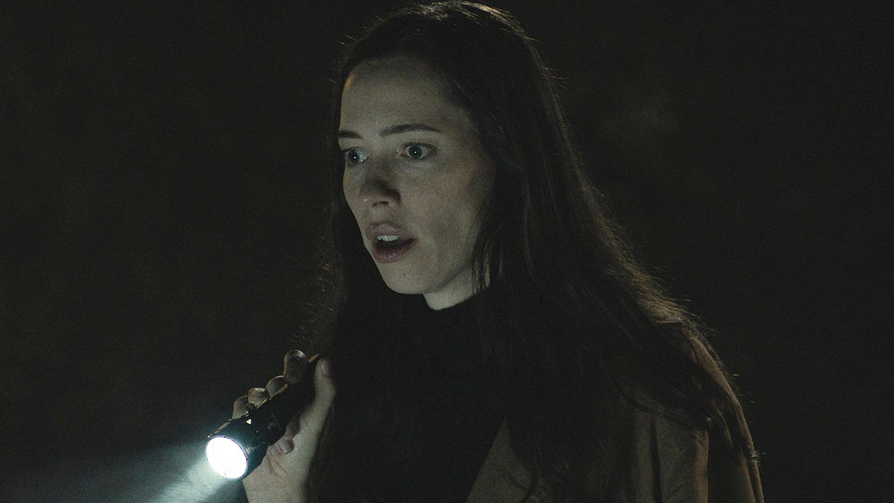 Rebecca Hall points a flashlight at something offscreen with a look of surprise on her face in the movie The Night House