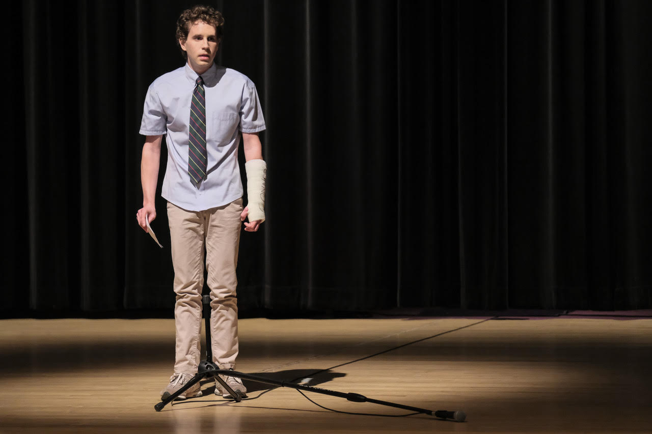 Ben Platt looking bewildered standing in the spotlight on stage with cards in his hand and a cast on his wrist in the movie Dear Evan Hansen