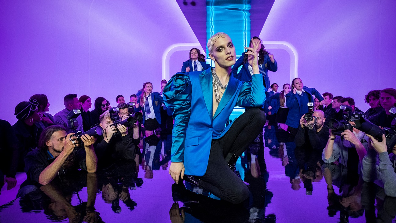 Max Harwood kneels on a fashion runway in a bright blue blazer during a musical number in the musical Everybody's Talking About Jamie