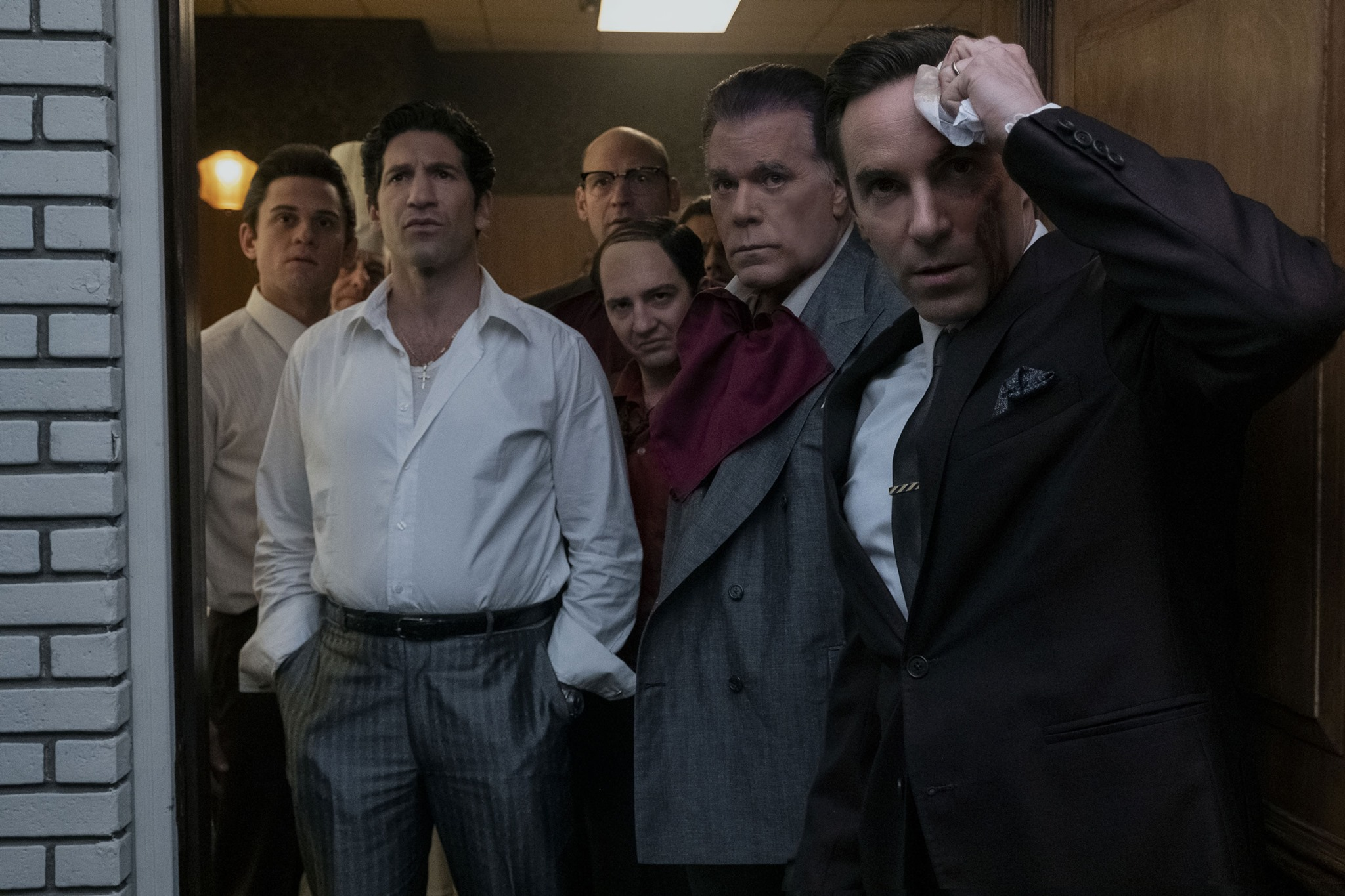 Billy Magnussen, Jon Bernthal, Corey Stoll, John Magaro, Ray Liotta, and Alessandro Nivola stand in a doorway looking out angrily in the movie The Many Saints of Newark