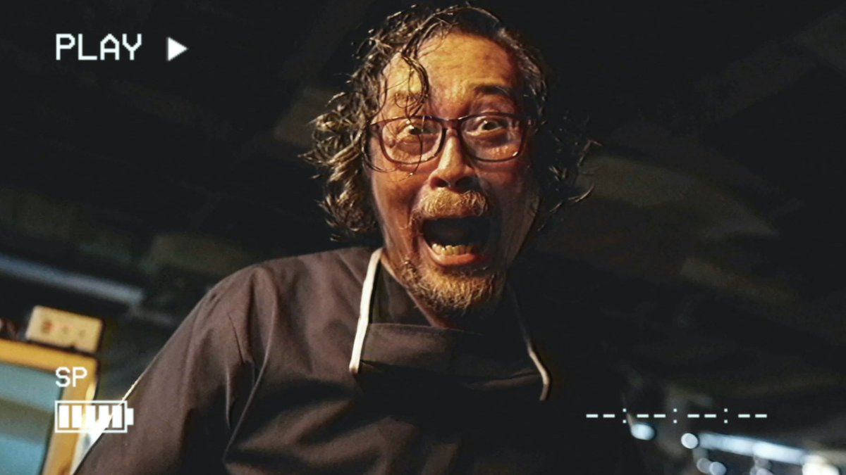 An Asian man with glasses laughing maniacally as he's being recorded through a video camera display in the horror anthology V/H/S/94